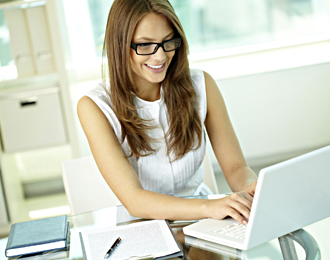 lady with glasses typing on laptop